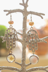 romantic earrings hanging on decorative background