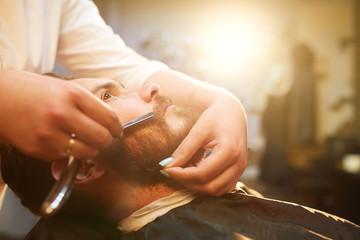Young handsome bearded man visiting barber shop. Barber concept.