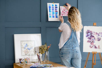 artist workspace decor. painting inspiration creation concept. woman sticking drawing and color swatch palette to the blue wall