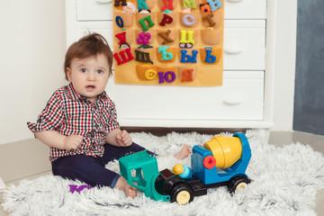 Child toddler boy playing with toys at home. Little boy sitting with toy car and looking at camera indoors against Russian alphabet on the background