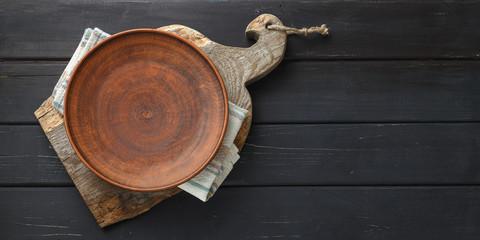 Empty clay plate on rustic cutting board