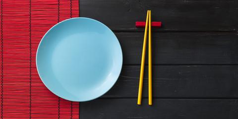 Empty plate and chopsticks on dark background