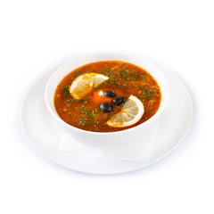 Tomato soup with olives and lemon slices on a white plate. Isolated