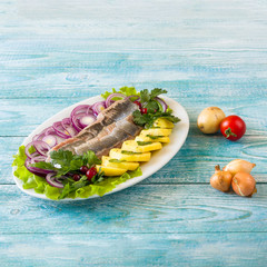 herring with potatoes on blue wooden background