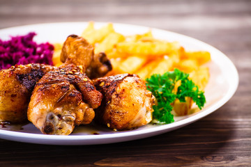 Roast chicken drumsticks with chips and vegetables