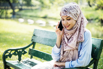 Islamic woman using mobile phone with smiling at park