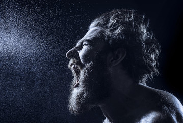 A bearded man angrily screams into a spray of water against a black background. Toned image.