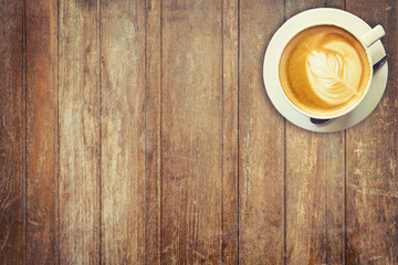Latte coffee cup on wood table background with space.