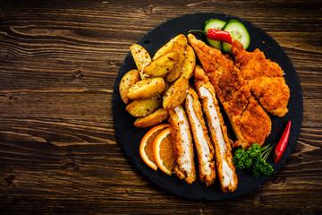 Fried pork chop, baked potatoes vegetables