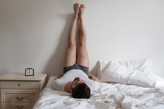 Man doing stretching in the bed for backache.