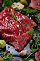 Flat lay of raw beefsteak with vegetables, herbs and spicies on metal tray, close-up, selective focus