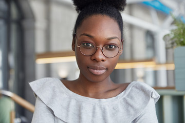 Close up shot of attractive serious female with dark skin, looks confidently directly at camera, wears round spectacles, poses in office, has break after work. Lovely African woman in eyewear