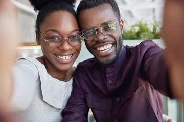 Two young funny African American wonk students, wear big glasses, take selfie on unrecognizable mobile phone, photograph themselves for profile publication in social networks, enjoy free time together