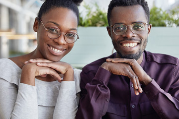 Successful dark skinned male and woman colleagues have pleased expressions, happy to recieve salary or be promoted at work, sit close to each other. Smiling attractive African woman and her partner
