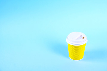 Bright yellow disposable safe heat resistant double walled paper take out cup of coffee to go. Colorful eco-friendly cardboard mug for hot beverages, white cap on blue background, close up, copy space