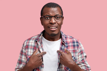Pleased African American young man wears white t shirt and checkered shirt, indicates at clothing with blank space for your advertising content isolated over pink background. Stylish dark skinned male