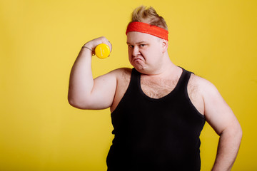 Fat man shows his muscle while holding dumbbell in hand