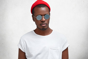 Portrait of fashionable hipster guy in trendy eyewear, red hat and casual white t shirt, gong to meet with friends, has serious confident look, poses against concrete wall. People, ethnicity, style