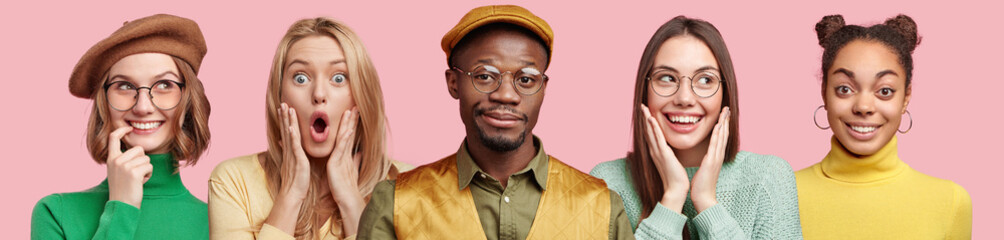 Photo of dreamy beautiful young female in beret and round spectacles, shocked amazed blonde woman, funny dark skinned male and overjoyed delighted women pose all together against pink background