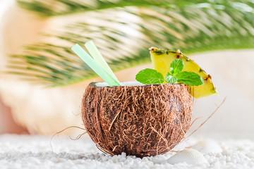 Fresh pinacolada in coconut on white pebbles