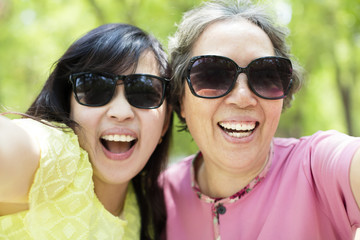 happy senior mother and daughter taking selfie.