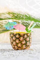 Fresh drink in pineapple on sandy beach on white pebbles