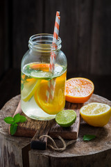 Water with citrus fruits and mint leaves on old stump