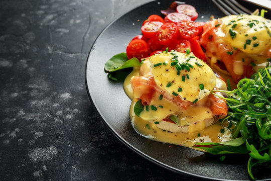 Eggs Benedict on english muffin with smoked salmon, wild rocket and hollandaise sauce in a black plate.