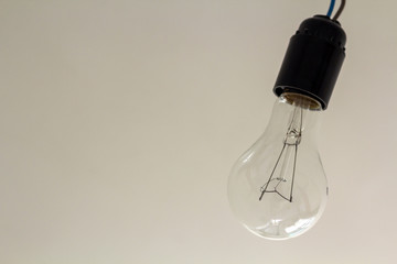 Close up picture of isolated electric light bulb on gray abstract background. Energy saving and economy concept.