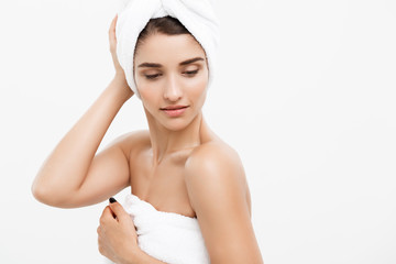 Beauty and Skin care concept - Beautiful caucasian Young Woman with bath towel on head covering her breasts, on white.