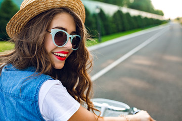 Closeup portrait of cute girl with long curly hair in hat  driving a bike on road. She wears  jerkin, blue sunglasses. She is smiling to camera, view from back.