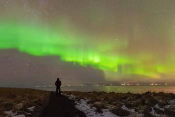 Aurora Borealis (Northern Lights) phenomenon in winter.Photographer standing under Aurora Polaris solar storm above his head at night in iceland