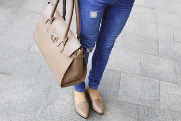 Woman in ripped blue jeans and brown leather shoes