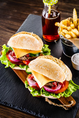 Tasty cheeseburgers with french fries served on fashionable black stone plate