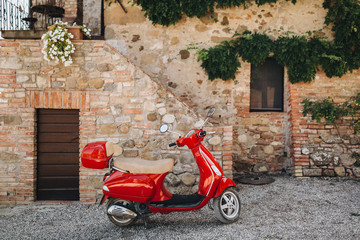 Scooter In the courtyard of an old house in Italy there is a red scooter