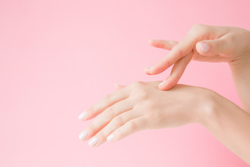Beautiful, groomed woman's hand touching her perfect, smooth skin. Care about clean and soft hands skin. Beauty concept. Pink background.