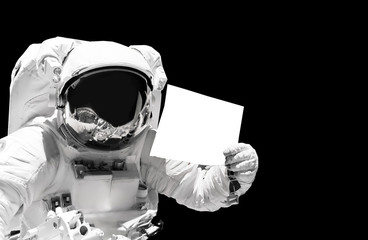 Astronaut close up holding a blank sheet of paper. Spaceman in outer space. Elements of this image furnished by NASA