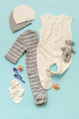 set of children's clothes for the newborn boy and girl on a blue background: body, cap, mittens. Collection spring-summer