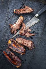 Barbecue spare ribs St Louis cut with hot honey chili marinade sliced as top view on an old burnt board with copy space