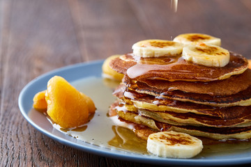 Pile of homemade pancakes with banana and walnuts on blue background, selective focus