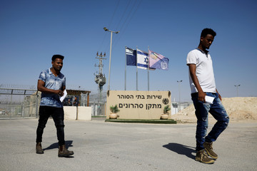 African migrants walk out after being released from Saharonim Prison in the Negev desert