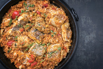 Traditional Louisiana fish jambalaya dish creole cajun with rice and tomatoes as top view in a pot with copy space right