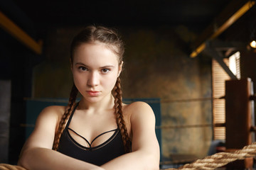 People, youth, sports, leisure, hobby and active lifestyle concept. Picture of self determined young muscular woman wearing black top staring at camera with serious look, resting during workout
