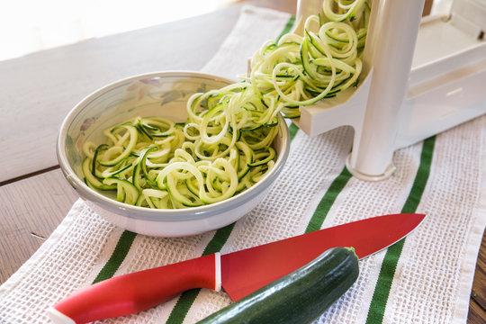Spiral zucchini noodles called zoodles prepared in spiralizer kitchen gadget