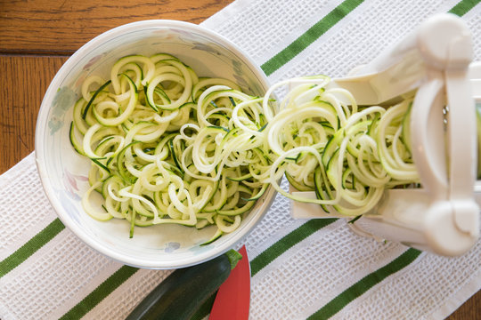 Spiral zucchini noodles called zoodles prepared in spiralizer kitchen gadget