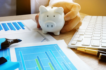 Wealth and savings concept. Man in office holding piggy bank.