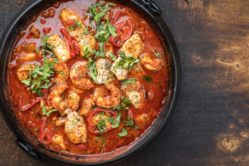 Traditional Creole cajun court bouillon with fish and seafood gumbo chowder stew as top view in a pot with copy space right.