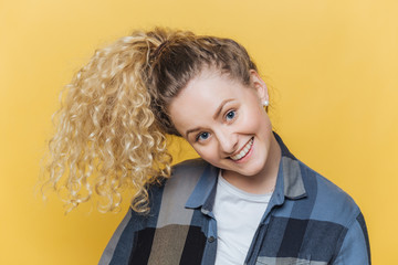 Funny cute female model with curly blonde pony tail, has positive smile, has fun alone indoor against yellow background, wears casual checkered shirt, being in good mood. Facial expressions.