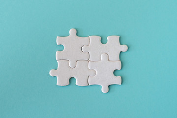 Wall Mural - four white details of puzzle on blue pastel background