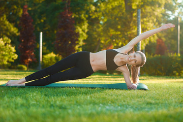 Photo of young sporty girl making yoga figures on the grass. Having slim stunning figure, wearing sport clothes in black and grey colors. Green summer or spring city park on background.